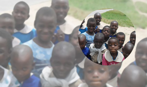 African children gathered on the grass smiling for the camera